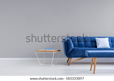Grey room with blue couch, bench and side table