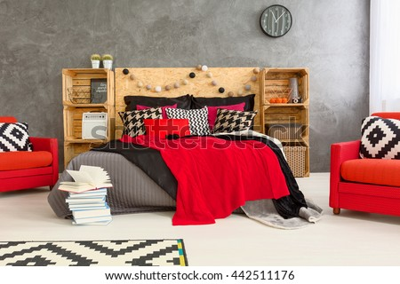 Grey room with double bed with wooden headboard. Red comfortable armchairs and wooden shelves in spacious bedroom #442511176