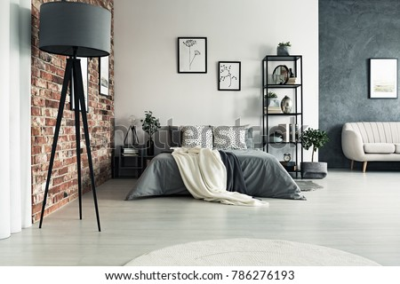 Grey roomy apartment with king size bed, sofa, lamp and one decorative brick wall