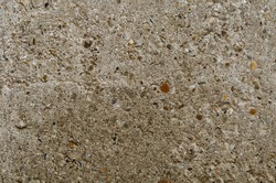 Grey rustic concrete wall background with small pebble. Ground stone for design with copy space