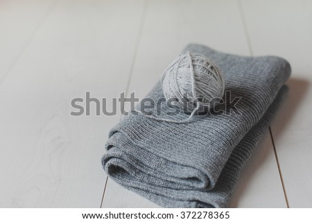 Grey scarf and ball of gray yarn on a white table. #372278365