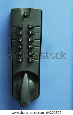 Grey security numbered door lock against blue door