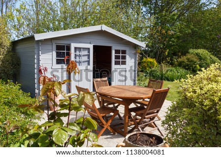 Grey shed with terrace and wooden garden furniture in a garden during spring