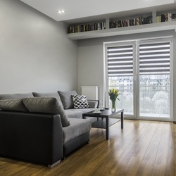 Grey sofa and coffee table in bright apartment relaxing space