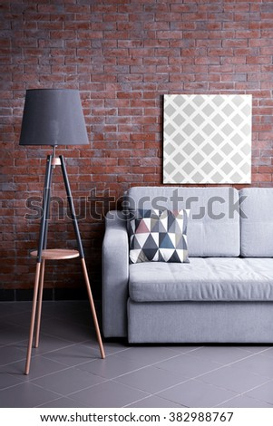 Grey sofa and floor lamp against brick wall in the room