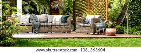 Grey sofa with decorative cushions and basket with pillows placed next to wicker armchair standing on wooden terrace