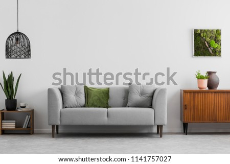 Grey sofa with pillows next to wooden cupboard in living room interior with lamp and poster. Real photo #1141757027