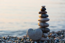 Grey stone in shape of heart in front of balanced stones on still water background