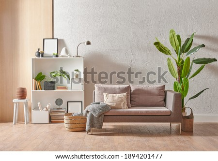 Grey stone wall interior room with wooden decor, bookshelf, sofa and vase of plant, middle table, carpet, home decoration.