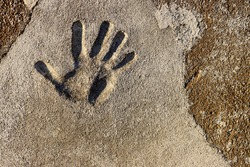 Grey stone wall with a human hand right palm print mark