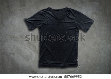 Grey t-shirt on concrete wall background.