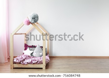 Grey tear-shaped pillow on pink satin coverlet on scandi bed against white wall in girl's bedroom #756084748