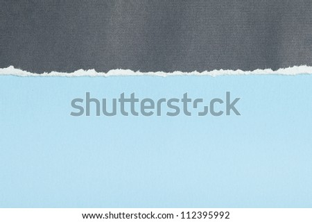 Grey textured paper with torn edge on blue background