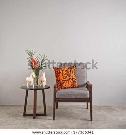 Grey upholstered chair in living room with flowers  #177366341