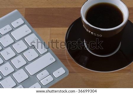 Grey wireless keyboard with white keys. Brown espresso mug. On wooden table top.