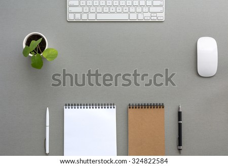 Grey Wooden Desk with Stationery and Electronics Classic Tone Wood Background Opened and Folded Beige Notepads Small Green Plant  Computer Mouse and Keyboard Top View