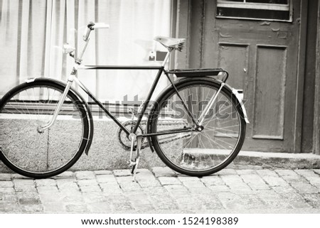Greyscale image of a bicycle in a cobbled street leaning against a wall of a building alongside an entrance door