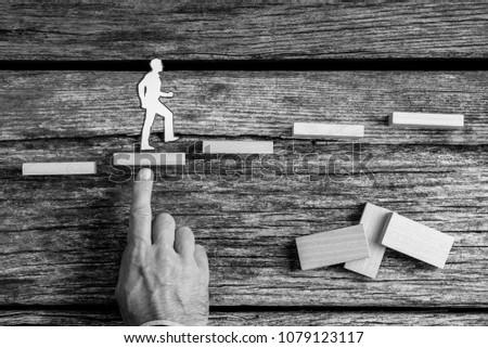 Greyscale image of businessman climbing the steps in a conceptual image with silhouette cutouts of a man and a human hand helping him climb over rustic wood. #1079123117