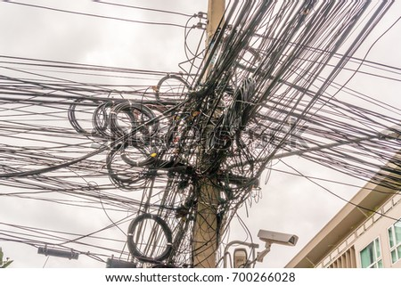 Grid of electric cables on the street of Thailand #700266028