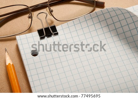 Grid paper with binder, glasses, and pencil over clip board background