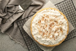Grid with delicious coconut cream pie on grey table