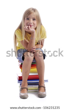 Gril seated on a stack of books. Isolated on white background
