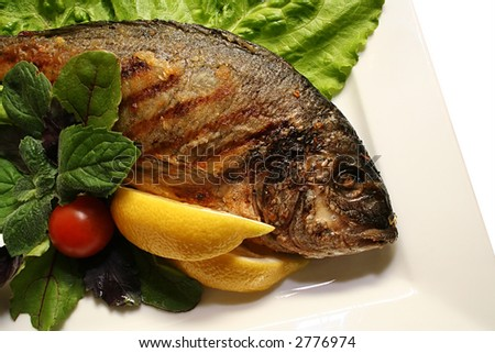 Grill a fish with salad on a dish