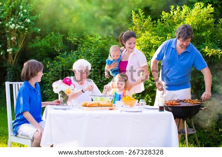 Grill barbecue backyard party. Happy big family, mother, father, age son, cute toddler daughter and baby, enjoying BBQ lunch with grandmother eating grilled meat in the garden with salad and bread.