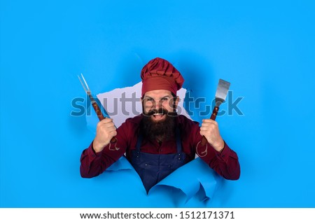 Grill cook. Chef man with BBQ cooking tools. Barbecue chef looking through paper hole. Picnic&barbecue. Cooking meat in park. Barbecue master. Chief cook in workwear with utensils for barbecue grill.