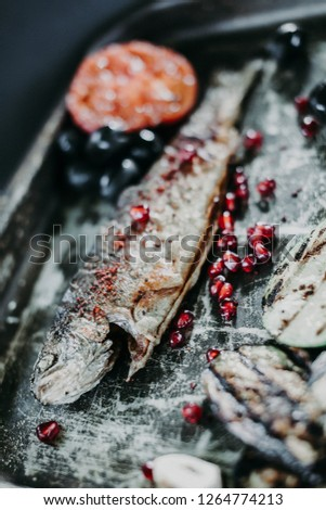 Grill fried trout fish with a spices on it with a grill fried tomato, zucchini, pomegranate seeds and herbs on the steel metal texture frying tray. Shallow focus. #1264774213