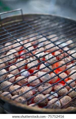 Grill grate with glowing coals in the background