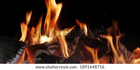 Grill Pit With Glowing And Flaming Hot Charcoal. Glowing Hot Charcoal In Barbecue Grill Pit With Flames Background Texture, Close-up. Flaming Charcoal In Grill Pit Isolated On Black Background.