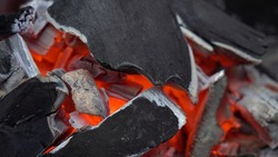 grill preparation concept. close-up of hot coals on the grill during the day. nobody.