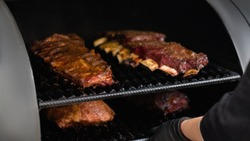 Grill restaurant kitchen. Closeup of chef cooking poultry, beef and pork meat, ribs in BBQ smoker.