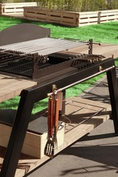 Grill Table. Outdoor Backyard BBQ Charcoal Grill Appliance. Family Garden Party Barbecue Grill, Closeup View. Green Backyard Lawn In The Background.