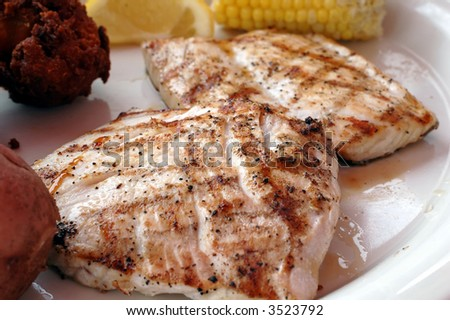 Grilled amberjack with corn, hush puppies, and lemon slice.