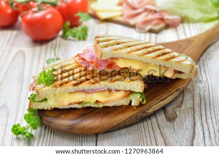 Grilled and pressed toast with smoked ham, cheese, tomato and lettuce served on wooden cutting board