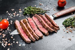 Grilled and sliced flat iron rare steak. Marble beef meat. Black background. Top view