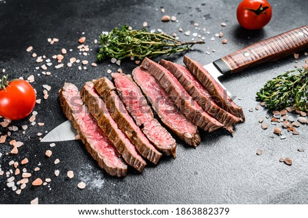 Grilled and sliced flat iron rare steak. Marble beef meat. Black background. Top view ストックフォト ©