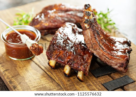 Stock Photo Grilled and smoked ribs with barbeque sauce on a carving board