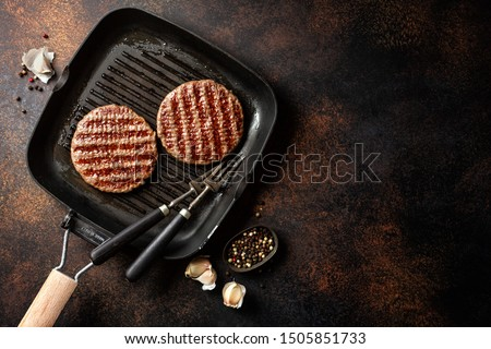 Grilled appetizing burger meat patties with spices on grill pan. Dark brown background. Top View.