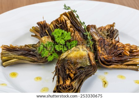 Grilled artishokes with parsley on the wood background #253330675