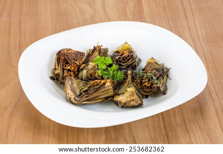Grilled artishokes with parsley on the wood background #253682362
