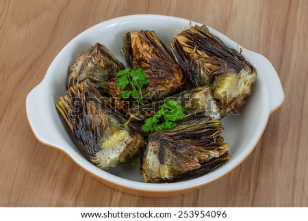 Grilled artishokes with parsley on the wood background #253954096