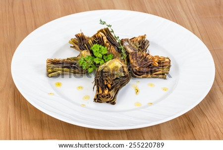 Grilled artishokes with parsley on the wood background #255220789