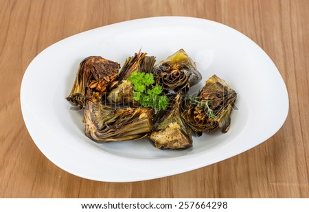 Grilled artishokes with parsley on the wood background #257664298