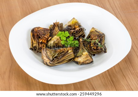 Grilled artishokes with parsley on the wood background #259449296