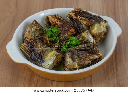 Grilled artishokes with parsley on the wood background #259757447