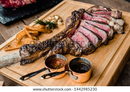 Grilled Australian tomahawk steak on wood plate with potato and garlic fried