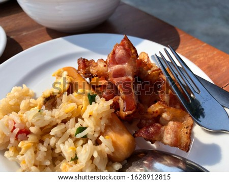 Grilled Bacon rice sausage American Asian mix breakfast healthy foodies quality meal hotel meal outdoor eating with stainless fork and spoon